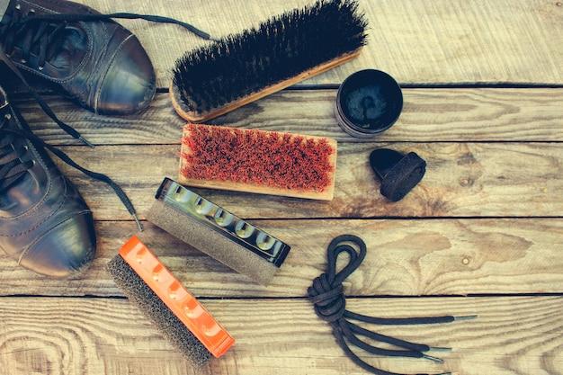Sapatos e produtos para o cuidado de calçados em fundo de madeira.