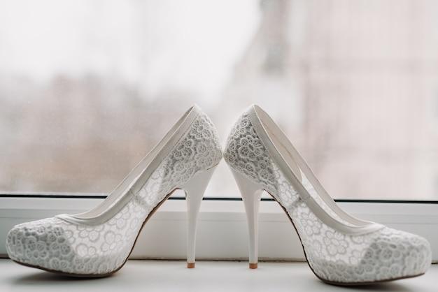 Sapatos elegantes de casamento branco da noiva com renda