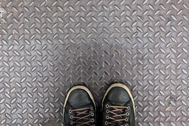 Sapatos em textura de placa de ferro diamantada como pano de fundo