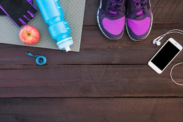 Sapatos esportivos; celular; fone de ouvido; garrafa de agua; luva; maçã e fita métrica na mesa de madeira