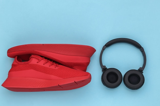 Sapatos esportivos com fones de ouvido estéreo em um fundo azul. vista do topo