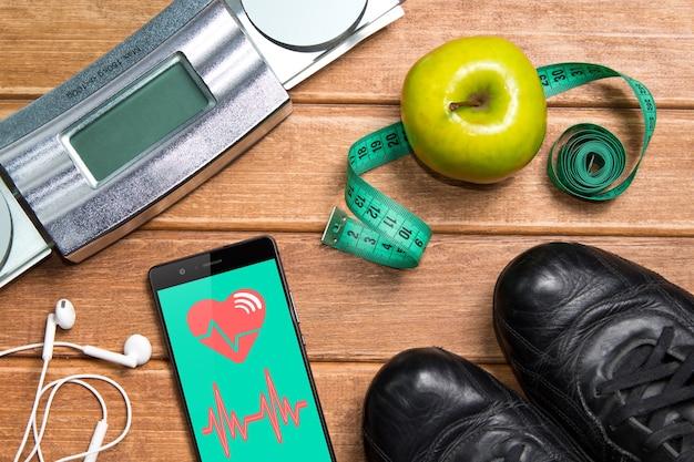 Sapatos esportivos, maçã, balanças e um telefone com cartão de saúde em uma mesa de madeira