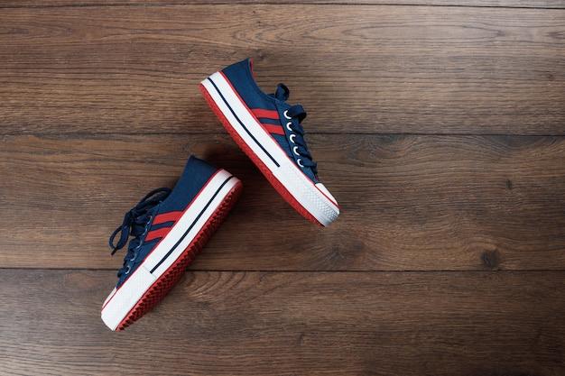 Sapatos esportivos masculinos em um escuro de madeira