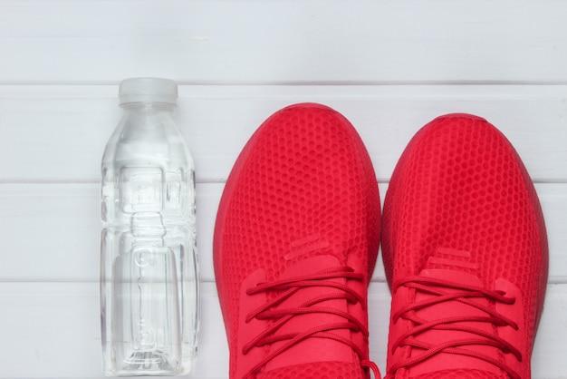 Sapatos esportivos vermelhos para correr, garrafa de água no piso de madeira branco. vista do topo.