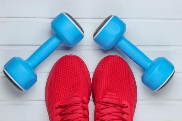 Sapatos esportivos vermelhos para treinamento, halteres no piso de madeira branco. vista do topo.