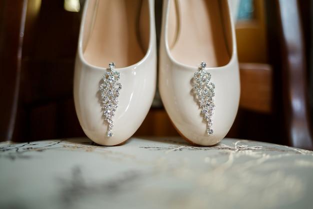 Sapatos femininos brancos, brincos de prata