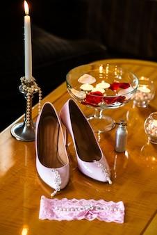 Sapatos femininos, brincos e vela