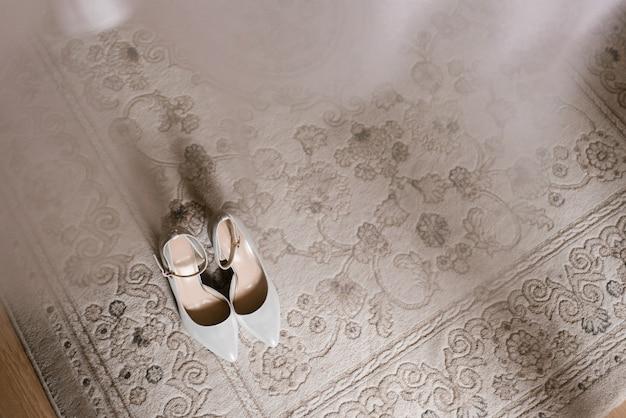 Sapatos femininos cinza abertos no tapete com uma cópia do espaço. manhã da noiva