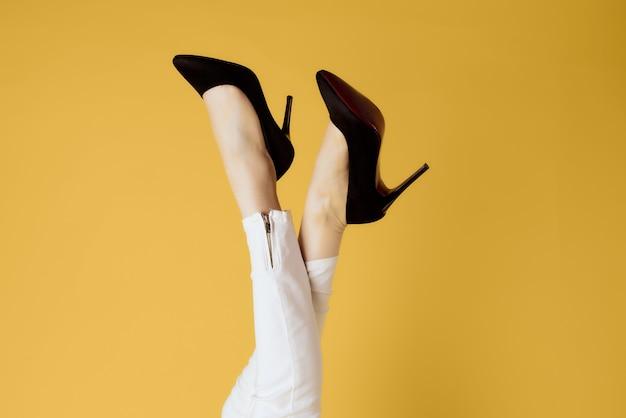 Sapatos femininos de cabeça para baixo posando com vista recortada de fundo amarelo