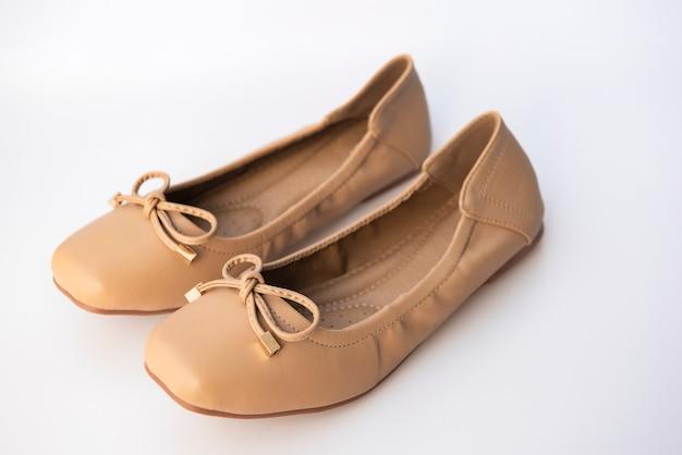Sapatos femininos de cor creme, colocados em uma parede branca