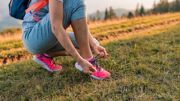Sapatos femininos de pé e esporte de alpinista ou corredor fazendo exercícios ao ar livre.