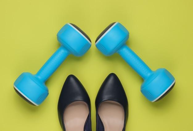 Sapatos femininos de salto alto esporte leddys com halteres em fundo verde conceito de fitness e moda