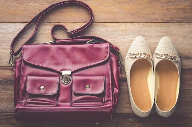 Sapatos femininos e sacos de couro pendurados colocados sobre um piso de madeira.