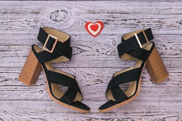 Sapatos femininos elegantes de camurça e um coração em uma superfície de madeira