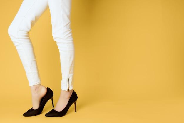 Sapatos femininos pretos cortados com vista de fundo amarelo posando