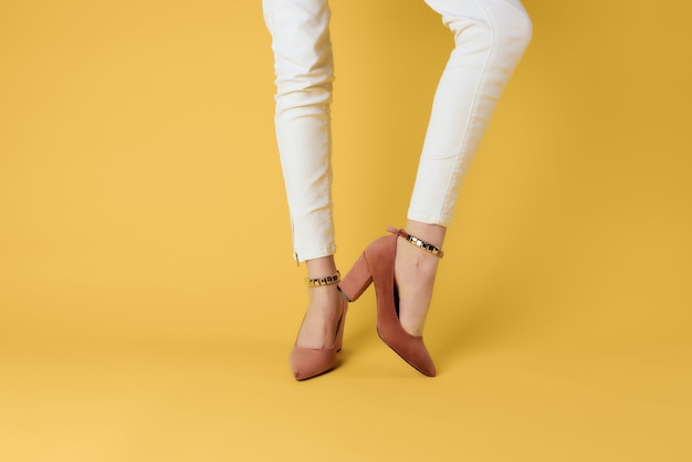 Sapatos femininos, temporadas da moda posando com fundo amarelo