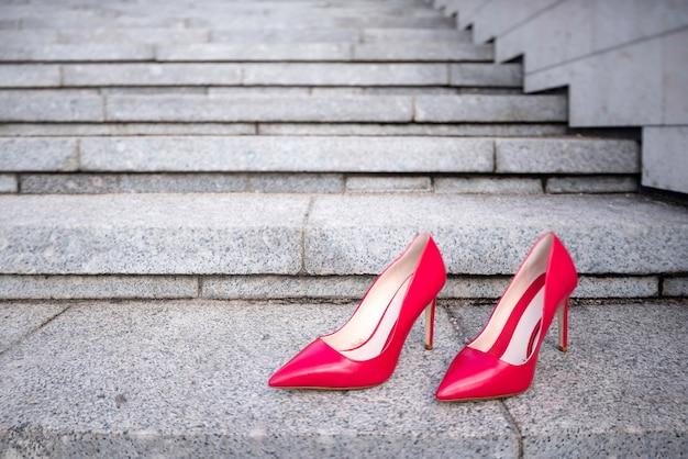 Sapatos femininos vermelhos de salto alto na escada