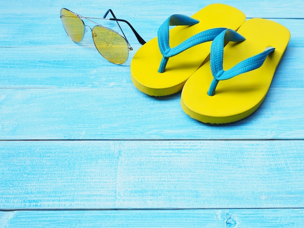 Sapatos flip flop amarelo e óculos escuros sobre fundo azul de madeira