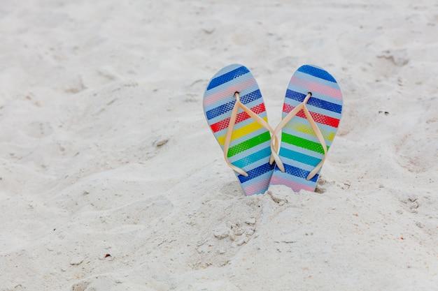 Sapatos flip flops em listras de cor em uma areia branca.