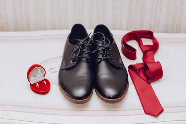 Sapatos, gravata e um anel de casamento
