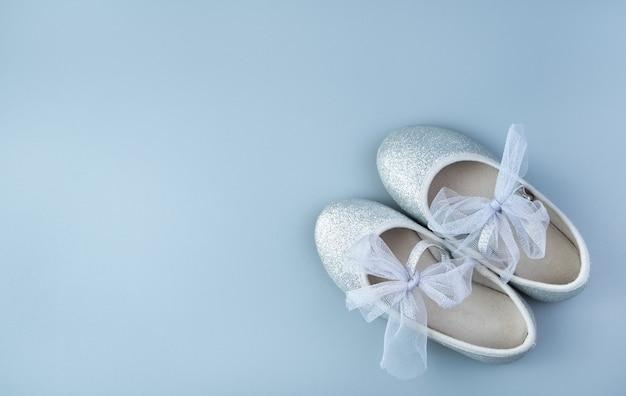 Sapatos infantis de prata do feriado sobre um fundo cinza-azulado.