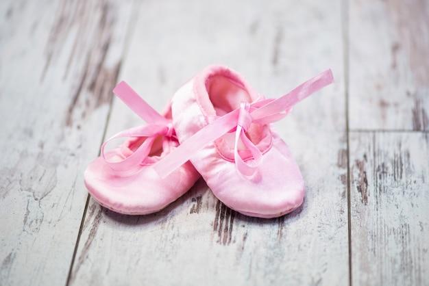 Sapatos infantis rosa em um fundo de madeira esperando a garota