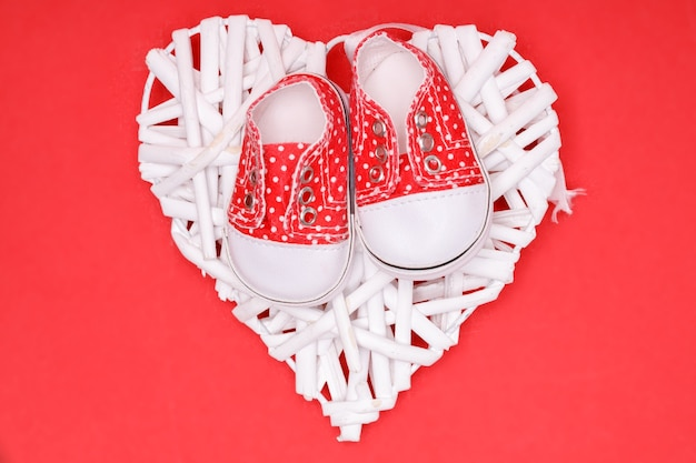 Sapatos infantis vermelhos com bolinhas brancas em um coração branco decorativo.