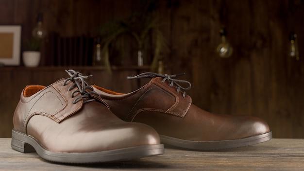 Sapatos marrons clássicos da moda masculina num piso de madeira.