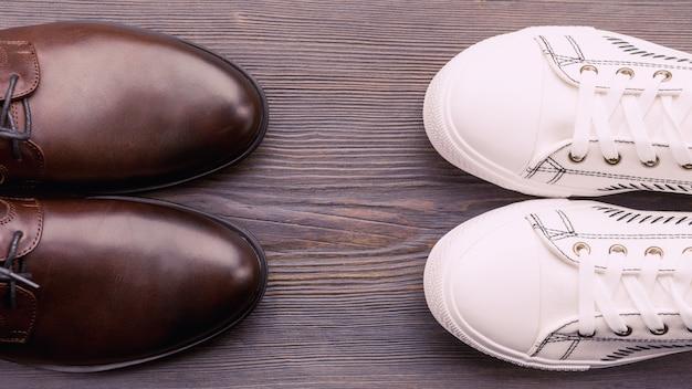 Sapatos marrons clássicos masculinos e tênis brancos sobre um fundo de madeira.