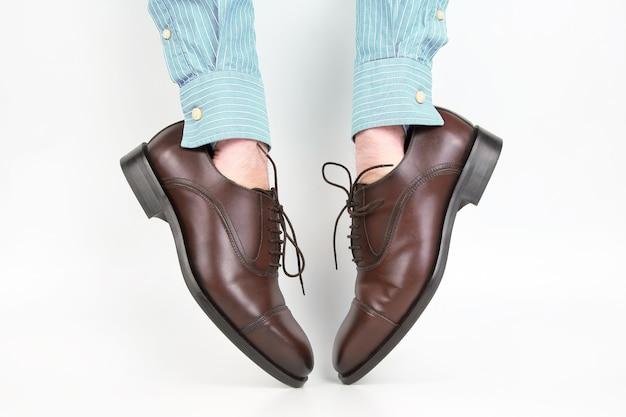 Sapatos marrons clássicos usados nas mãos em um fundo branco
