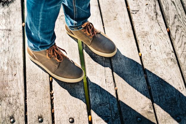 Sapatos marrons de um viajante na superfície de madeira lá fora.