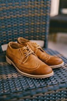 Sapatos marrons do noivo em um assento de cadeira em uma sala com profundidade de campo rasa.