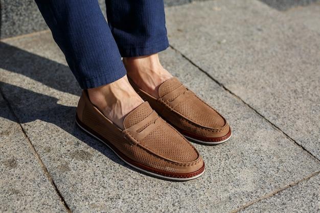 Sapatos marrons masculinos feitos de couro genuíno, close-up nos pés masculinos