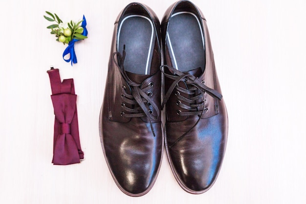 Sapatos masculinos, borboleta e lapela do noivo