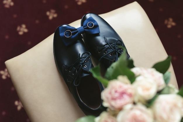 Sapatos masculinos, buquê, gravata e anéis em uma cadeira