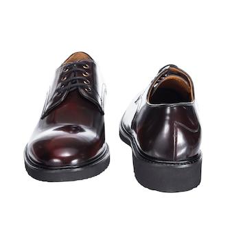 Sapatos masculinos clássicos de couro com atacadores, marrom de couro polido, isolados em uma superfície branca