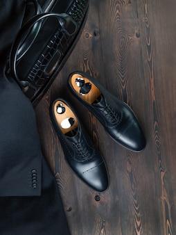 Sapatos masculinos clássicos em uma superfície de madeira ao lado de um portfólio de couro de crocodilo preto e uma jaqueta