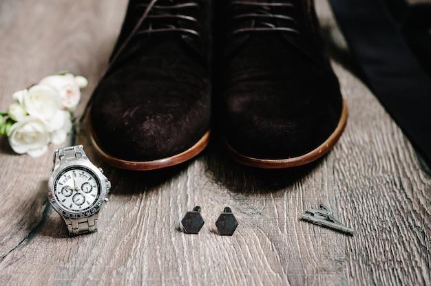 Sapatos masculinos de camurça elegantes, relógio, gravata, botões de punho, flor flor na lapela para noivo. acessórios de casamento em fundo de madeira marrom rústico. composição da ideia tradicional. conceito de férias. vista lateral