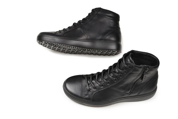 Sapatos masculinos de couro preto e uma câmera preta em um fundo branco isolado. copie o espaço.