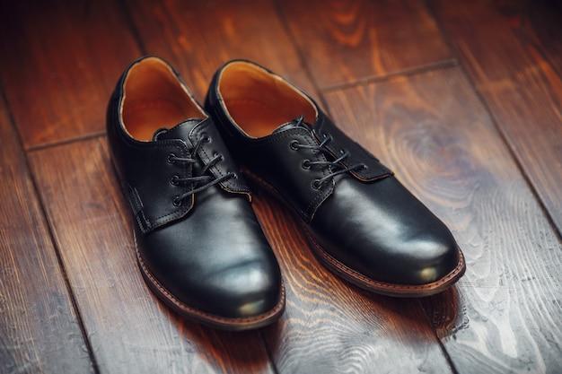 Sapatos masculinos de couro preto na superfície de madeira