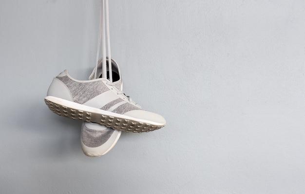 Sapatos masculinos de moda cinza com fundo de parede de tijolo
