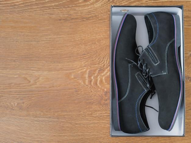 Sapatos masculinos elegantes em uma caixa em um piso de madeira.