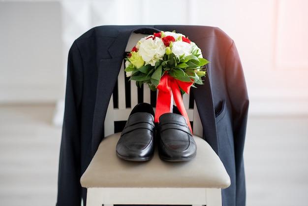 Sapatos masculinos em uma cadeira com um buquê