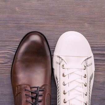 Sapatos masculinos marrons clássicos e tênis brancos em madeira