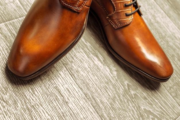 Sapatos masculinos marrons no chão de madeira