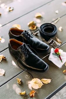 Sapatos masculinos negros com cadarços desamarrados ao lado de um cinto e lapela do noivo no chão de madeira