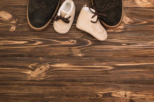Sapatos masculinos perto de botas de criança