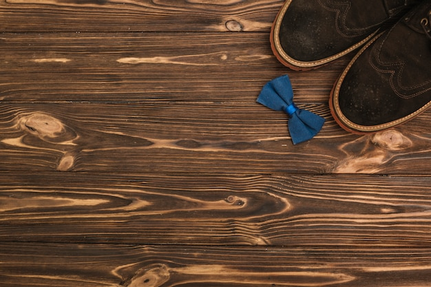 Sapatos masculinos perto de gravata borboleta