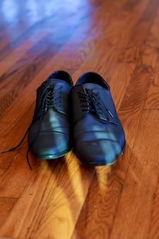 Sapatos masculinos pretos brilhantes para a noiva, jogados no chão sapatos masculinos deitados no chão