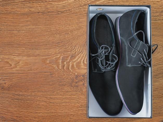 Sapatos masculinos pretos na caixa no chão de madeira.